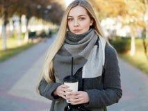 Fin extérieure vers le haut de tir de femme blonde élégante de l'année 20s dans l'écharpe sur le café ou le thé potable de pause  photographie stock libre de droits