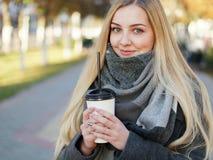 Fin extérieure vers le haut de tir de femme blonde élégante de l'année 20s dans l'écharpe sur le café ou le thé potable de pause  image stock