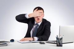 Fin frustrante d'homme d'affaires ses yeux à la main sur le fond gris Photographie stock libre de droits