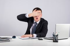 Fin frustrante d'homme d'affaires ses yeux à la main sur le fond gris Photo libre de droits