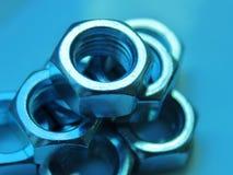 Fin industrielle d'abstraction d'?crous vers le haut de fond bleu brouill? image stock
