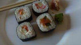 Fin japonaise de variété de petits pains de sushi tournant sur un plat blanc banque de vidéos