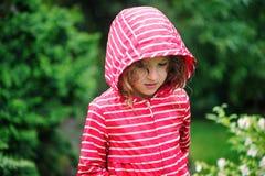 Fin mignonne de fille d'enfant vers le haut de portrait sous la pluie dans le jardin d'été Image stock