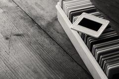 Fin noire et blanche vers le haut de l'image de vieux cadres de glissières et de vieil appareil-photo au-dessus de table en bois Photos stock