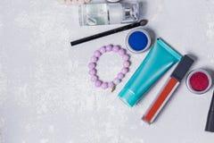 Fin professionnelle de maquillage sur le fond gris blanc, amorce, toner, crème, rouge à lèvres rouge, fard à paupières, bracelets Image stock