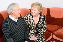 Fin supérieure heureuse de séance de couples ensemble sur un sofa Images stock