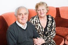 Fin supérieure heureuse de séance de couples ensemble sur un sofa Image libre de droits