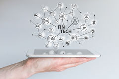 Fin Tech and mobile computing concept. Hand holding tablet in front of grey background Stock Images