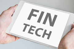 Fin tech text displayed on touchscreen of modern tablet or smart device. Concept of financial technology startup company Stock Images