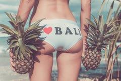 Fin tropicale sexy de bout de femme avec le fruit exotique d'ananas sur la plage de l'île de paradis de Bali Régime sain Photographie stock