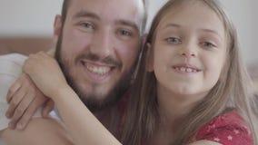 Fin vers le haut d'homme barbu bel de portrait et de fille positive mignonne regardant dans la caméra souriant, l'enfant étreigna clips vidéos
