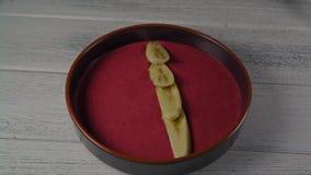 Fin vers le haut de banane femelle de diffusion de main sur le smoothie de fruit banque de vidéos