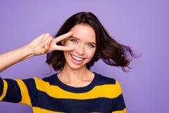 Fin vers le haut de beau génial étonnant de photo elle son v-signe main-bras de dame près d'oeil apprécient la coiffure assez com image libre de droits