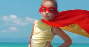 Fin vers le haut de belle petite fille de portrait dans le costume de super h?ros, habill? dans un manteau rouge et le masque du  clips vidéos