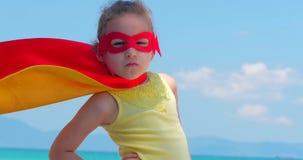 Fin vers le haut de belle petite fille de portrait dans le costume de super h?ros, habill? dans un manteau rouge et le masque du  banque de vidéos