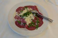 Fin vers le haut de Bresaola, de fromage et de Rocket Salad dans un plat blanc image stock