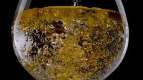 Fin vers le haut de bulle de Champagne en verre sur le fond noir photos stock