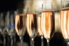 Fin vers le haut de bulle de Champagne en verre sur le fond noir images stock