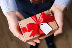Fin vers le haut de cadeau de Saint-Valentin de participation de l'homme dans des mains, ruban rouge, étiquette de cadeau, surpri photographie stock