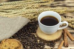 Fin vers le haut de café chaud avec des grains de café sur la table en bois photos stock