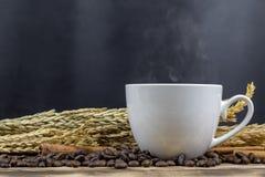 Fin vers le haut de café chaud avec des grains de café sur la table en bois image stock