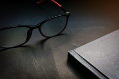 Fin vers le haut de carnet et de verres noirs sur le fond noir de bureau dans le ton de allumage dramatique r Le GR photo libre de droits