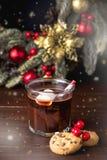 Fin vers le haut de chocolat chaud savoureux fait maison en verre avec la sucrerie de fête Cane Vertical Toned de fond de Noël de photos stock