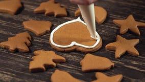 Fin vers le haut de garnir le coeur fait maison de pain d'épice Décoration des biscuits de Noël banque de vidéos