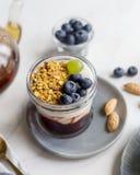 Fin vers le haut de granola avec la confiture, la crème et les baies dans le pot photo stock