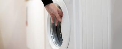 Fin vers le haut de l'ensemble et de la salle de bains b de lancement de main de blanchisserie de machine à laver de début à la m photos stock