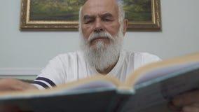 Fin vers le haut de l'homme supérieur barbu réfléchi de portrait s'asseyant à la table en bois sur le sofa en cuir lisant le livr clips vidéos