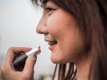 Fin vers le haut de la belle femme asiatique mettant le rouge à lèvres de maquillage, concept heureux de femme, cinématographique photo libre de droits