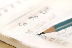 Fin vers le haut de manuscrit pour faire le plan de liste dans le petit carnet, extrem Photographie stock libre de droits
