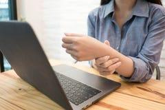 Fin vers le haut de massage de femme des employés sur sa main et bras pour la douleur de soulagement du fonctionnement dur Concep photos libres de droits