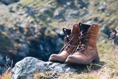 Fin vers le haut de nouvelle chaussure en cuir brune sur le point de vue de lac de montagne Concept d'aventure, randonneur, voyag images stock
