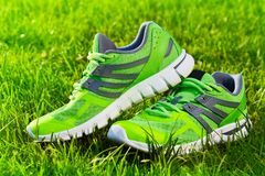 Fin vers le haut de nouvelles paires de chaussures de course vertes/de chaussures d'espadrille sur le champ d'herbe verte en parc images stock