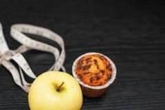 Fin vers le haut de pomme jaune Delicious avec le petit gâteau et la bande de mesure sur la table en bois noire photos stock