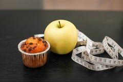 Fin vers le haut de pomme jaune Delicious avec le petit gâteau et la bande de mesure sur la table en bois noire photo stock