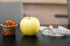 Fin vers le haut de pomme jaune Delicious avec le petit gâteau et la bande de mesure sur la table en bois noire avec l'espace de  photo stock