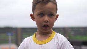 Fin vers le haut de portrait de visage : garçon mignon regardant et souriant la caméra se tenant - profondeur de champ banque de vidéos