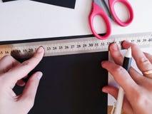 Fin vers le haut de tir - d?corateur de femme professionnelle, concepteur travaillant avec le papier d'emballage et faisant l'env image libre de droits