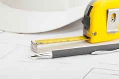Fin vers le haut de tir de studio du casque blanc de construction avec le crayon et la bande de mesure photographie stock libre de droits