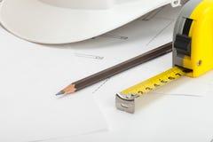 Fin vers le haut de tir du casque blanc de construction avec le crayon et la bande de mesure image libre de droits