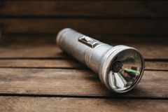 fin vers le haut de vieille lampe-torche en métal sur le fond en bois photos libres de droits