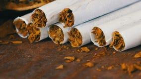 Fin vers le haut des cigarettes faites maison ou de la cigarette roulée d'OD à côté des feuilles sèches de tabac bourrées du taba banque de vidéos