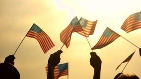 Fin vers le haut des drapeaux américains dans des mains de peuples banque de vidéos