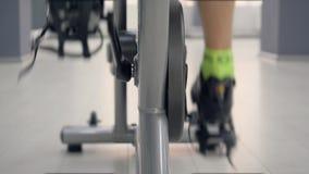 Fin vers le haut des jambes tournant des pédales sur le vélo statique à la classe de recyclage dans le gymnase, vue arrière banque de vidéos