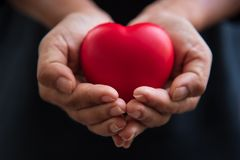 Fin vers le haut des mains donnant le coeur rouge comme donateur de coeur Saint Valentin de concept d'amour Charit? m?dicale de d photos stock