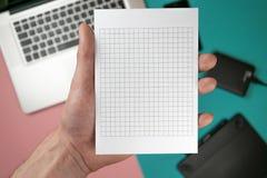 Fin vers le haut des mains masculines tenant le blanc de papier pour le papier de conception images libres de droits