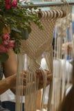 Fin vers le haut des mains tissant la tapisserie de macramé avec le fil beige photo stock
